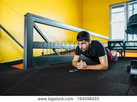 Sports and active lifestyle. man doing exercise strap - Plank standing on his elbows at the gym. It notes the time on the phone.
