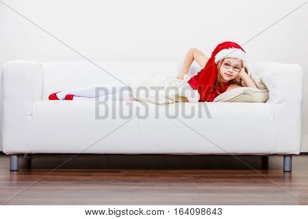 Girl family time during christmas. Cute little lady laying on sofa. Small girl lying on the couch. Resting time wearing red santa claus hat and shoes.