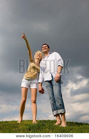 Feliz pareja joven mirando algo sobre un verde prado. Hombre Mostrar algo a mano
