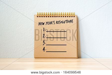 Concept New Year's Resolutions on notepad on wood table