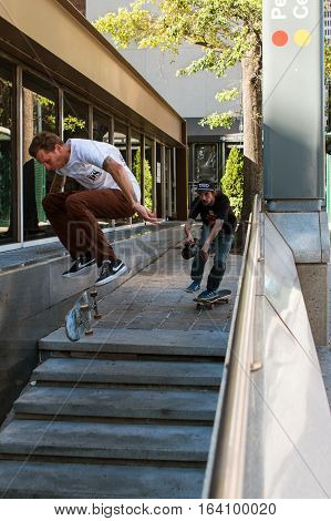 ATLANTA, GA - OCTOBER 2016:  A man attempts a difficult skateboard trick over concrete steps while a friend films it outside a MARTA train station in downtown Atlanta in Atlanta GA on October 8 2016.