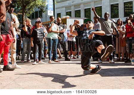 ATLANTA, GA - OCTOBER 2016:  A young man spontaneously break dances as spectators watch as part of a b-boy battle at Atlanta Hip Hop Day at Woodruff Park in Atlanta GA on October 8 2016.