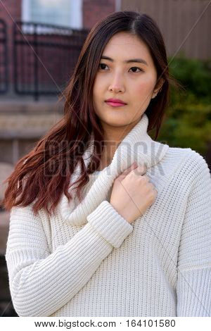 Portrait of a beautiful young Asian model in the park during a chilly day.