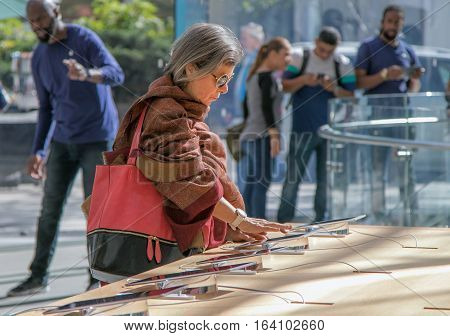 New York October 5 2016: An elderly woman is looking at an iPad tablet in the Apple store on Manhattan's Upper West Side.