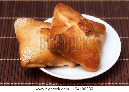 Two pasties stuffed meat on bamboo napkin close up
