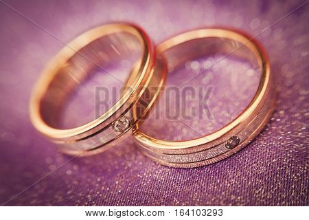 Two beautiful golden wedding rings with brilliants close-up. Selective focus