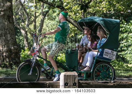 New York, June 25, 2016: A man operating a rickshaw is giving a tour to New York City visitors in Central Park.