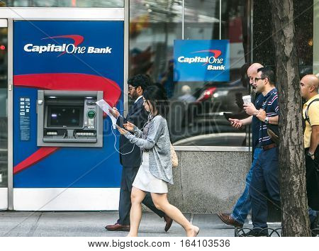 New York, July 19, 2016: A Capital One ATM on the streets of Manhattan with people walking by.