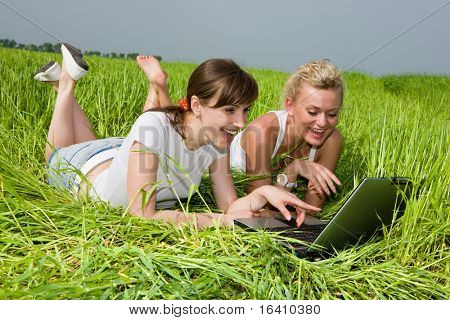 Two beautiful girls in white clothes are laughing near laptop computer outdoors. Lay on the green grass