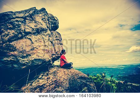 Side view of asian woman sitting on boulders and looking far away on sky with cloudy over tranquil nature at the daytime. Freedom concept. Beauty landscape from national park. Cross process vintage effect.