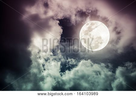 Attractive photo of a nighttime sky with cloudy and bright full moon. Beautiful nature use as background. Outdoors. Cross process tone. The moon were NOT furnished by NASA.