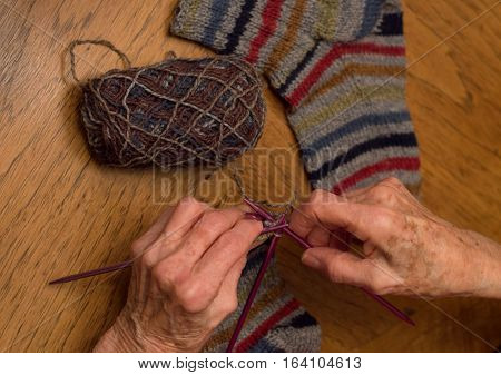 Close up of elderly woman's hands knitting socks with fuchsia needles and variegated yarn on wooden table. Shallow depth of field.