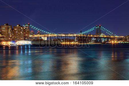 Williamsburg bridge by night, spanning the East River between Brooklyn and Manhattan Manhattan and Williamsburg bridges span across the East River between Manhattan and Brooklyn boroughs.