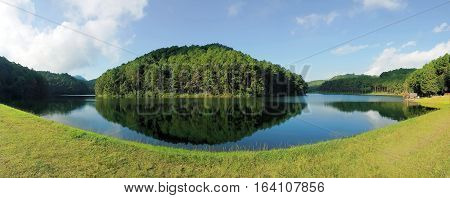 Panorama view of reflection of pine trees in Pang Oung Lake Mae Hong Son Thailand