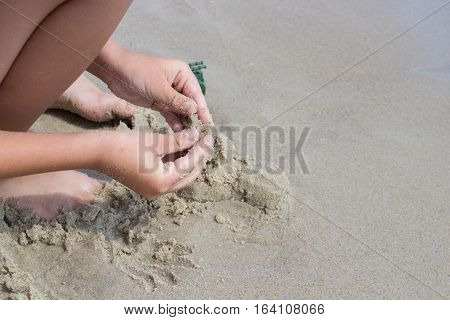 sand on the beach boy playing hands