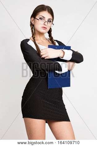 sexy secretary, portrait of beautiful brunette business lady with glasses and wearing in pinstripe suit. holds a plate for notes