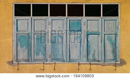 Blue vintage wooden window on yellow cement wall