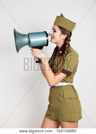 sexy fashionable woman in military uniform and garrison cap, holding bullhorn and screaming.