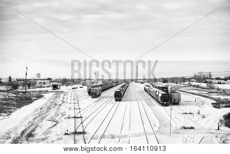 Industrial railway shipping cars docked at a yard site surrounded by houses and industrial buildings on the outskirts of a city in black and white winter landscape