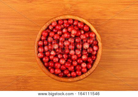 Lingonberry (Vaccinium vitis-idaea) in dish on wooden background