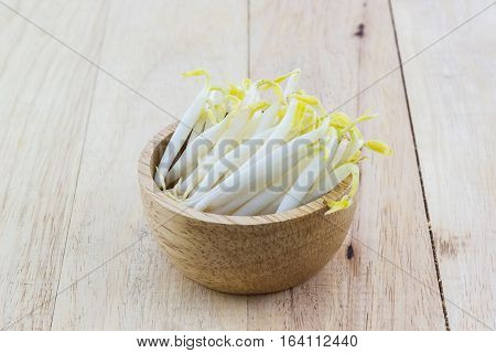 Bean sprout in the wood bowl on wood background.