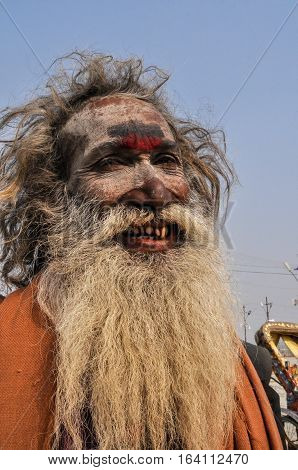 Allahabad Uttar Pradesh India- 15 January 2013: Smile of An Aghori Sadhu with long hairs ash and holy mark on face wearing human bones and rudraksha bead at Mahakumbh mela Allahabad Uttar Pradesh India. The Aghori are known to engage in post-mortem ritual