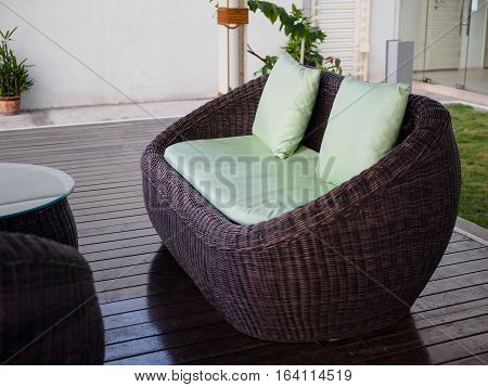 closeup brown chair with green pillow of Patio Furniture set