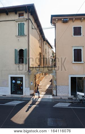 VERONA,ITALY- September 08 2016: The woman (local citizen) is walking (hurrying up) on the street of Verona