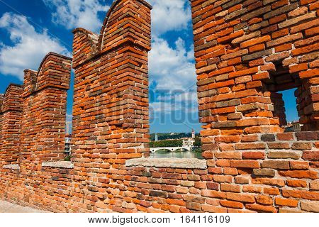 VERONA, ITALY- September 08 2016: The fortifications and battlements of Scaligeri Bridge (Ponte Scaligero) are made of bricks stretching over the river Adige now only used as a pedestrian walkway. Ponte Scaligero (Castelvecchio Bridge) is built in the sec