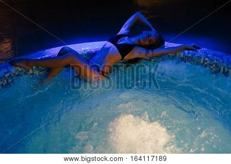 Beautiful young Sexy woman lying down on edge of Jacuzzi
