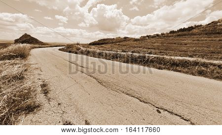 Old Asphalt Road between Mown Wheat Field in Sicily Vintage Style Sepia