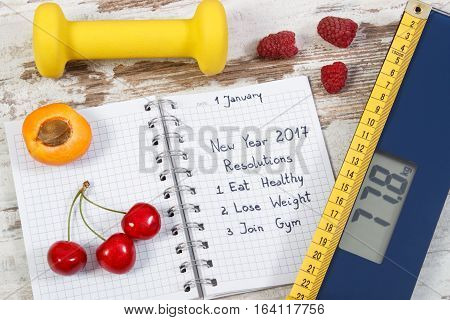 Electronic Bathroom Scale And New Year Resolutions Written In Notebook