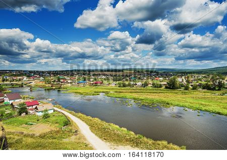 Beautiful landscape with a village located on the banks of the river on a summer day. Russia. Ural. The Village Of Staroutkinsk