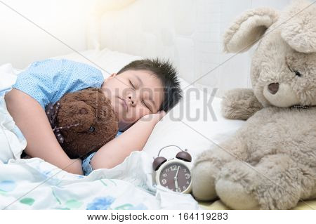 fat boy asleep and hugging bear on bed