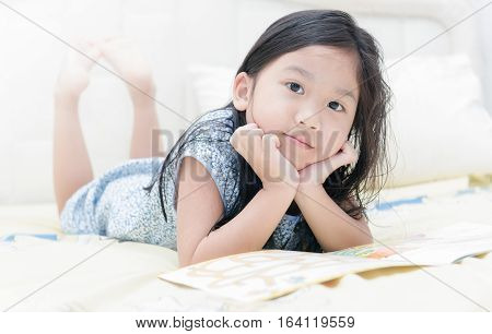 Cute little asian girl in nightdress reading a book and smiling while lying on bed in the bedroom.