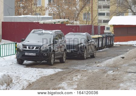 SARANSK, RUSSIA - JANUARY 1, 2017: Nissan X-Trail and Infiniti FX parked at city street. Photo taken at cloudy day.
