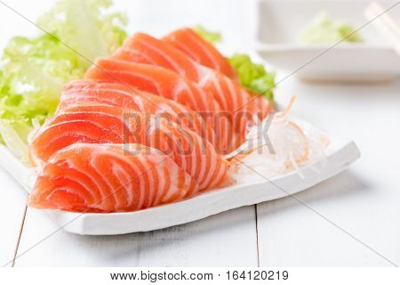 Salmon Sashimi On White Dish And Wood Background