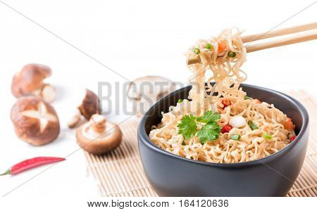 Closed Up Instant Noodles With Vegetables On Chopstick Isolated
