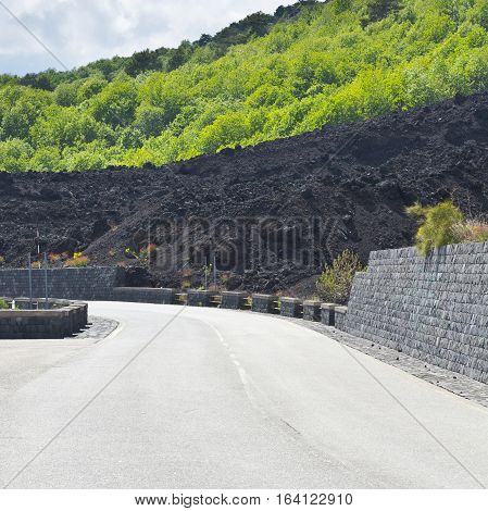 Asphalt Road between the Lava and Bush Covered Slopes of Mount Etna in Sicily