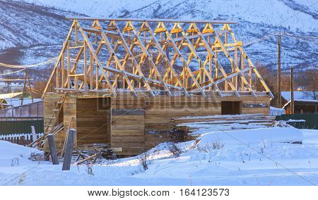 Rural house under construction. Winter. View front