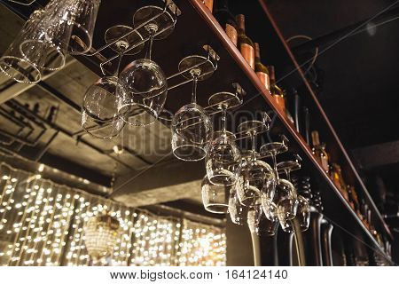 Wine glasses in shelf above a bar rack in restaurant.