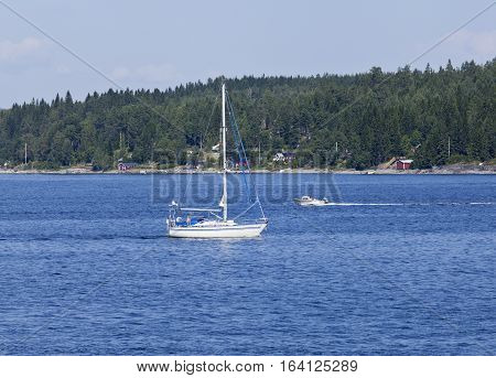 BALTIC SEA, SWEDEN ON JULY 26. View of a sailboat, motorboat and the seaside by the coast on July 26, 2013 at the Baltic Sea, Sweden. Unidentified people. Editorial use.