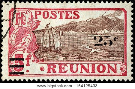 LUGA RUSSIA - NOVEMBER 29 2016: A stamp printed by REUNION shows view of commune St. Rose and the volcano. Reunion is an island and region of France in the Indian Ocean circa 1924.