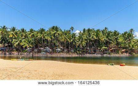 Heavenly spot in tropical greens of palm trees. Beach lodges under a foliage shadow the sandy beach with canoe and young people along the mouth of the river going to the ocean.