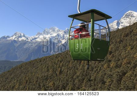 Lijiang China - November 11 2016: Cable Car on foreground with some tourists inside and Jade Dragon Snow Mountain on foreground. The Jade Dragon Snow Mountain in Yunnan it's the southernmost glacier in the northern emisphere.