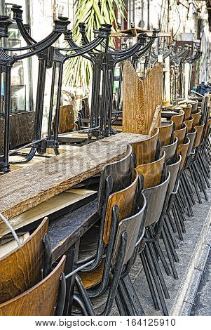 Metal Legged Bistro Chairs with Wooden Seats Stacked Outside a Bar in Israel City of Jaffa