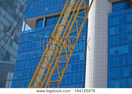Crane and building under construction in Tel-Aviv. Industrial construction crane in Israel.