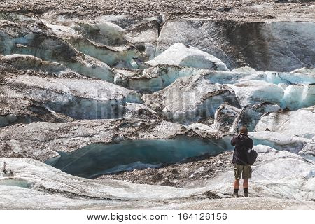 Man photographing glacier. Photographer in mountains takes photo