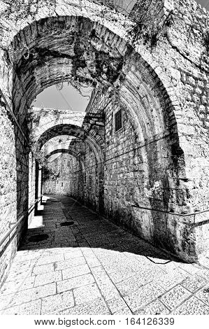 Narrow Alley in the Armenian Quarter of Jerusalem. Cobbled street among traditional stoned houses in old Jerusalem. Black and White Picture