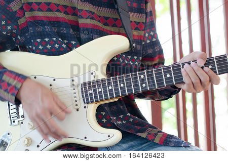 Young Living and practicing electric guitar happily at home.